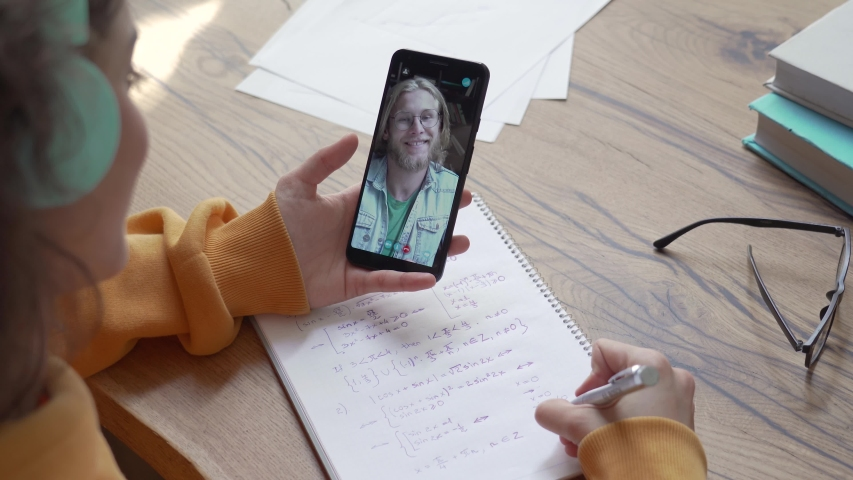School student teen girl holding smart phone zoom video calling male teacher tutor on screen using mobile videochat application distance learning online class write notes. Over shoulder closeup view. Royalty-Free Stock Footage #1053511208