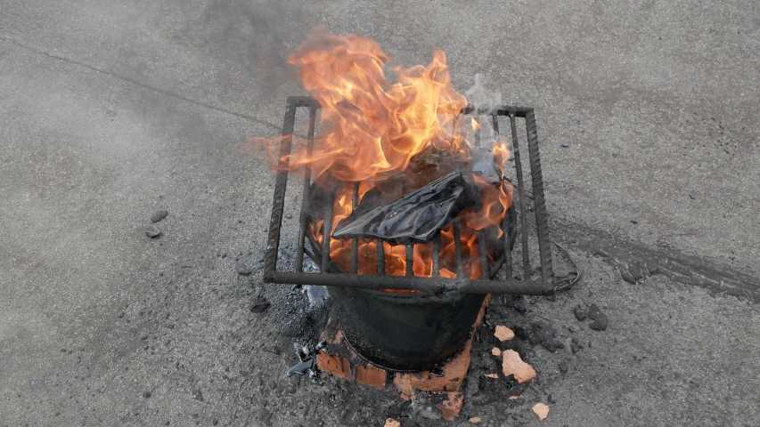 Molten hot tar in a bucket on the bricks. Roof repair. Fire from bucket. Grid on bucket. | Shutterstock HD Video #1053511574