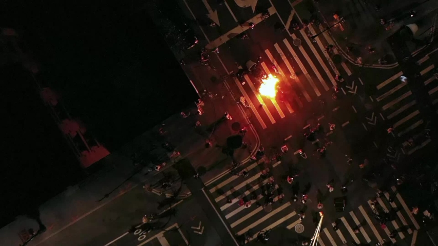 NEW YORK - MAY 30, 2020: protestors riot burning small isolated fire in intersection on street at night to protest police killing of George Floyd in New York City NYC.