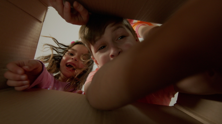 Little Pretty Girl And Two Boys Look In Cardboard Box. Inside View. They Are Happy And Surprised. Children Pull Their Hands Into The Box. Royalty-Free Stock Footage #1053515387