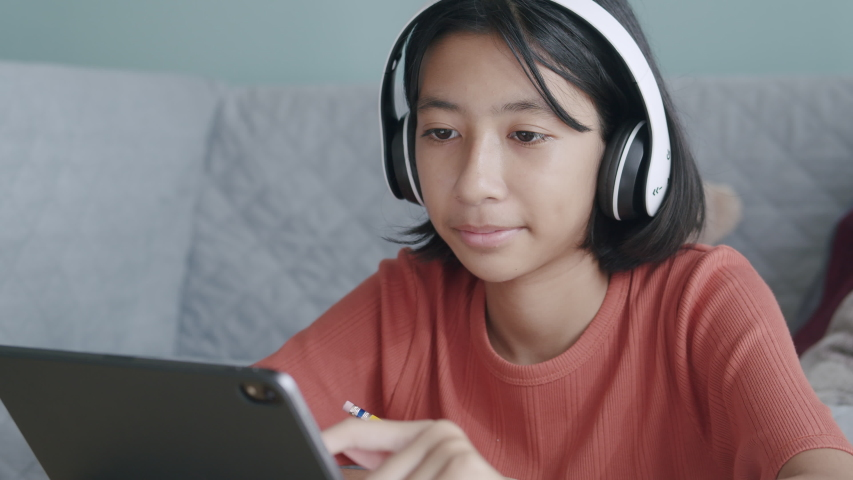 Asian girl is study online via the internet on tablet with headphone while sitting at home morning, Asia Children find information studying on Digital tablet. Concept of online learning at home Royalty-Free Stock Footage #1053515609