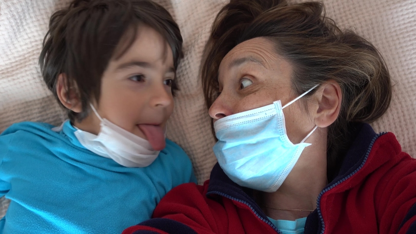 4K Covid-19 isolation selfies - Comic mother and child in masks grimace and make faces on camera