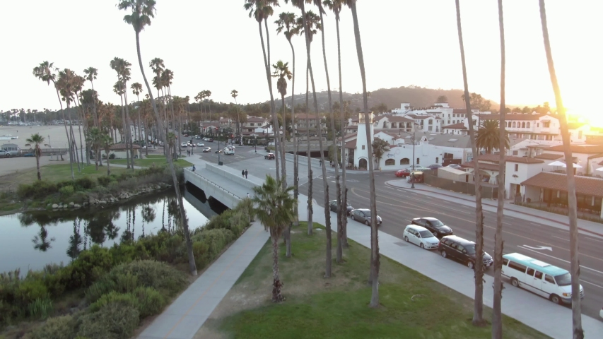 Rising aerial shot of Santa Barbara overseeing colonial style buildings and a major local road during a sunset. Palm trees are in the foreground with small hills and white buildings in the background.
