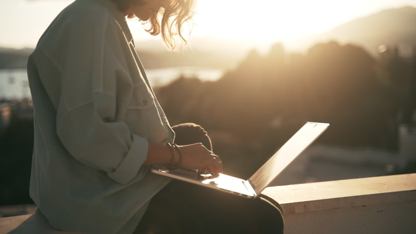 Close-up shot of a yang woman typing on a laptop keyboard while sitting on the roof terrace with a city view at the sunset time. Royalty-Free Stock Footage #1053520526