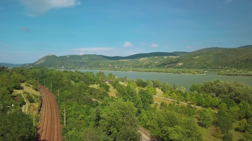 Aerial drone view in the turn of the river Danube in Hungary over Nagymaros. Railway lines   Shutterstock HD Video #1053523922