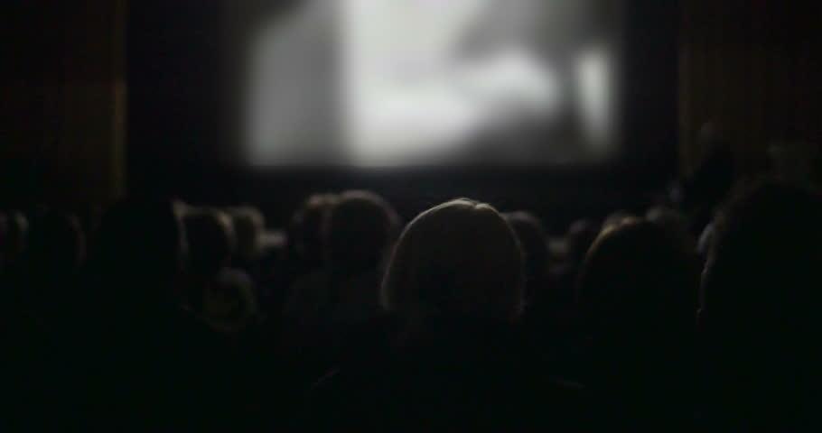 Back view of people watching movie in the cinema. Defocused screen with film lightening viewers in dark hall  | Shutterstock HD Video #10535243