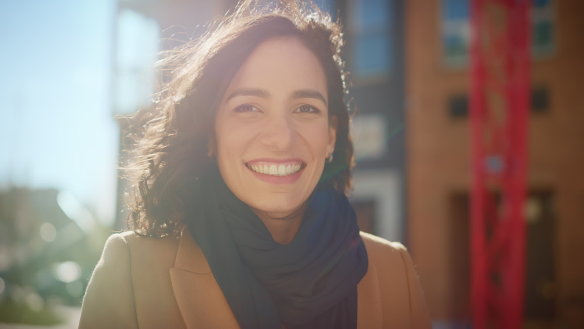Portrait of a Gorgeous Dark Haired Hispanic Woman Smiling Charmingly while Standing in the Middle of Modern Urban City Landscape, Wearing Spring Coat. Happy Young Woman Enjoys Life