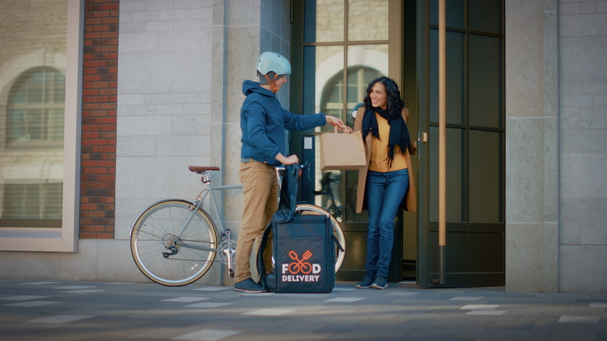 Happy Food Delivery Man Wearing Thermal Backpack Rides Bike to Deliver Restaurant Order to a Beautiful Female Customer. Courier Delivers Lunch to Gorgeous Girl in Modern City District Office Building Royalty-Free Stock Footage #1053526499