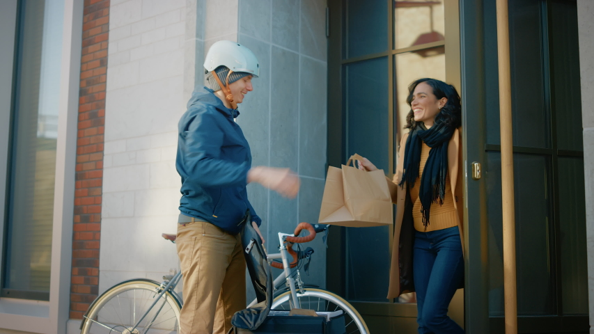 Happy Food Delivery Man Wearing Thermal Backpack on a Bike Delivers Restaurant Order to a Beautiful Female Customer. Courier Delivers Takeaway Lunch to Gorgeous Girl in Office Building. Side View Royalty-Free Stock Footage #1053526502