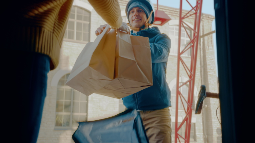 Female Customer Opens Door to a Happy Food Delivery Man Wearing Thermal Backpack on a Bike and Recieves Restaurant Order. Courier Delivers Takeaway Lunch to Gorgeous Girl. Inside Shot Royalty-Free Stock Footage #1053526505