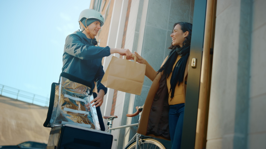 Happy Food Delivery Man Wearing Thermal Backpack on a Bike Delivers Restaurant Order to a Beautiful Female Customer. Courier Delivers Takeaway Lunch to Gorgeous Girl in Office Building. Low Angle Royalty-Free Stock Footage #1053526511