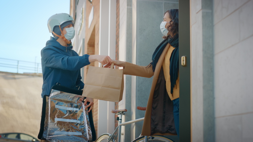 Food Delivery Man Wearing Protective Medical Face Mask and Thermal Backpack Rides a Bike to Deliver Order to a Masked Female Customer. Courier Delivers Takeaway Lunch. Quarantine, Social Distancing