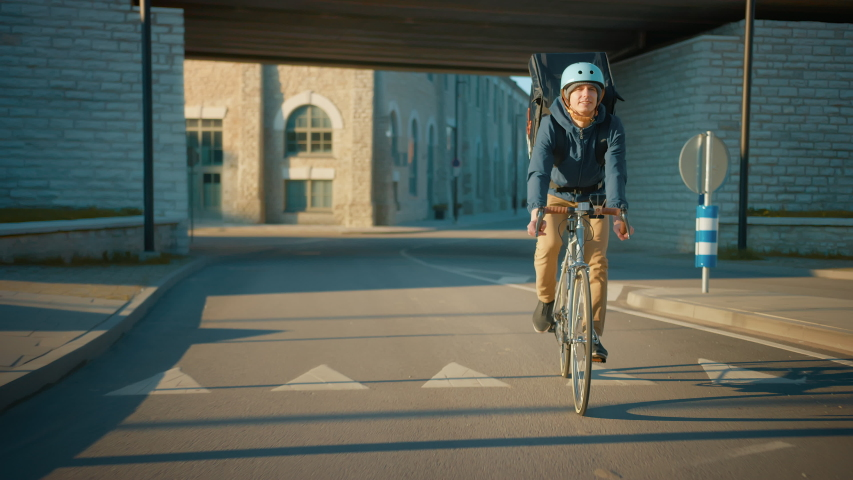 Happy Food Delivery Courier Wearing Thermal Backpack Rides a Bike on the Road To Deliver Orders and Packages for Clients. Sunny Day in Modern City with Stylish Urban Buildings. Front Following Shot Royalty-Free Stock Footage #1053526547