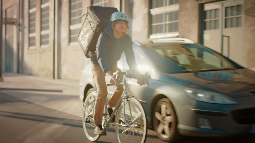 Happy Food Delivery Courier Wearing Thermal Backpack Rides a Bike on the Road To Deliver Orders for Clients and Customers. Sunny Day in Modern City with Stylish Urban Buildings. Front Following Shot | Shutterstock HD Video #1053526550