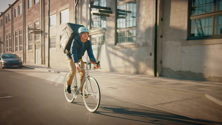 Happy Food Delivery Courier Wearing Thermal Backpack Rides a Bike on the Road To Deliver Orders for Clients and Customers. Sunny Day in Modern City District with Buildings. Slow Motion Front Followig Royalty-Free Stock Footage #1053526553