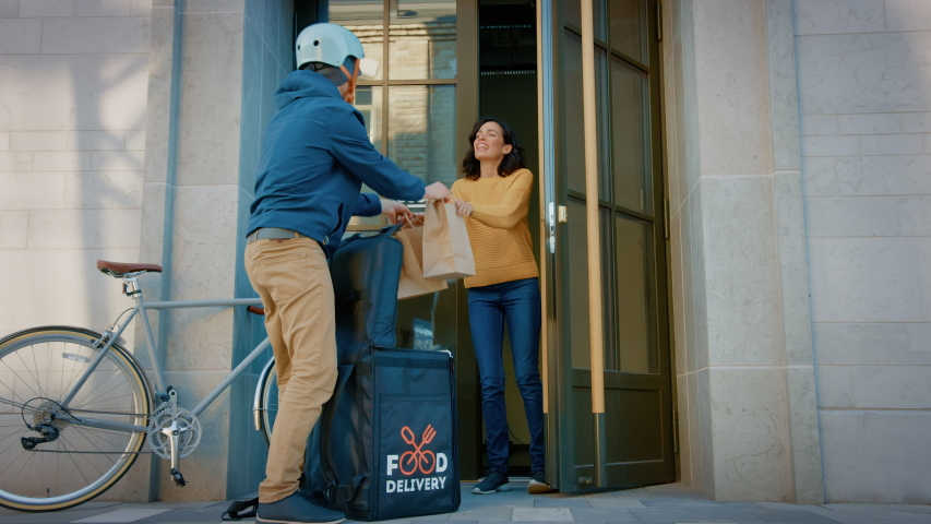 Happy Food Delivery Man Wearing Thermal Backpack on a Bike Delivers Restaurant Order to a Beautiful Female Customer. Courier Delivers Takeaway Lunch to Gorgeous Girl in Urban Office Building.Side View Royalty-Free Stock Footage #1053526556