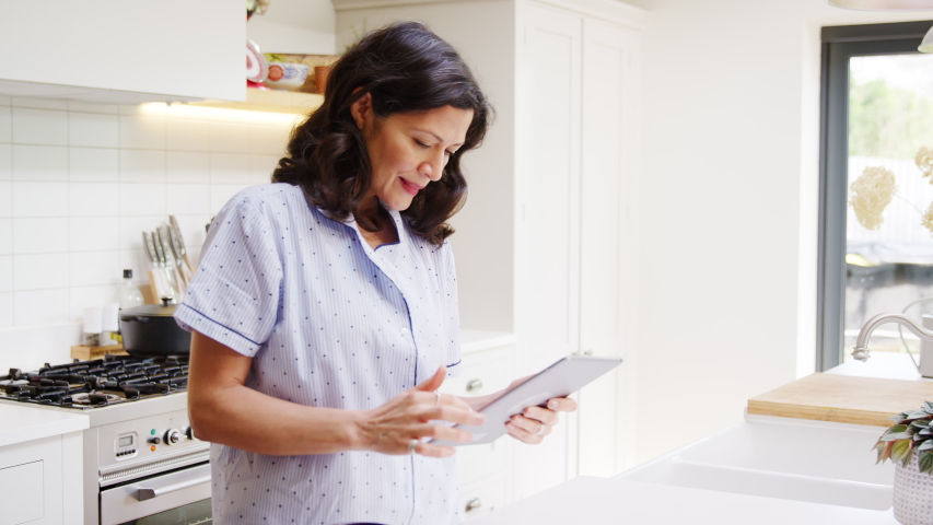 Mature woman at home in kitchen wearing pyjamas looking at digital tablet - shot in slow motion | Shutterstock HD Video #1053528071