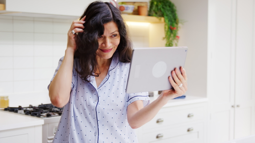 Mature Hispanic woman in pyjamas at home in kitchen checks hair and appearance with digital tablet - shot in slow motion | Shutterstock HD Video #1053528080