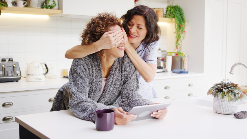 Gay mature woman wearing pyjamas surprises partner by covering her eyes as she looks at digital tablet - shot in slow motion | Shutterstock HD Video #1053528104