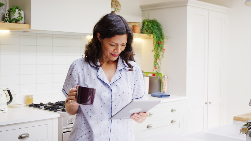 Mature woman at home in kitchen wearing pyjamas looking at digital tablet and drinking coffee - shot in slow motion | Shutterstock HD Video #1053528107