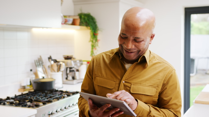 Smiling senior man at home in kitchen looking at digital tablet- shot in slow motion | Shutterstock HD Video #1053528434