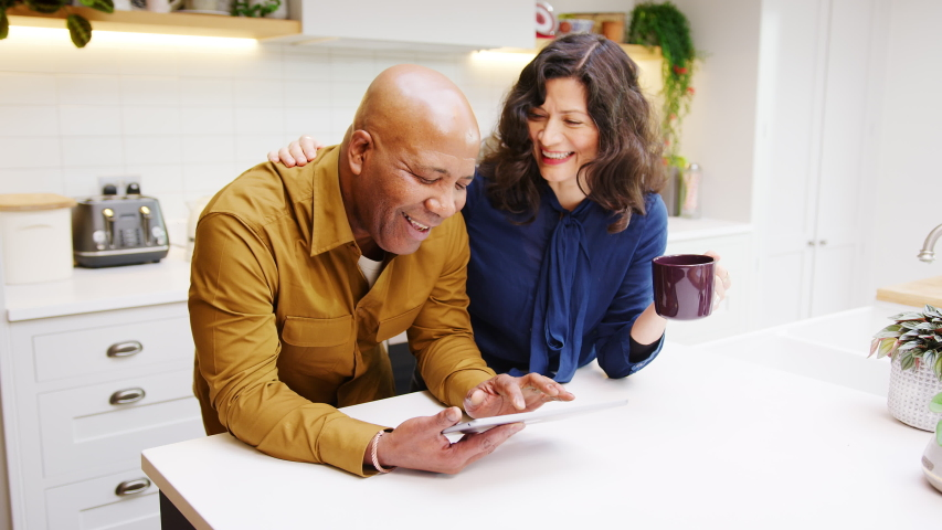 Mature couple at home in kitchen drinking coffee and looking at digital tablet together - shot in slow motion | Shutterstock HD Video #1053528443