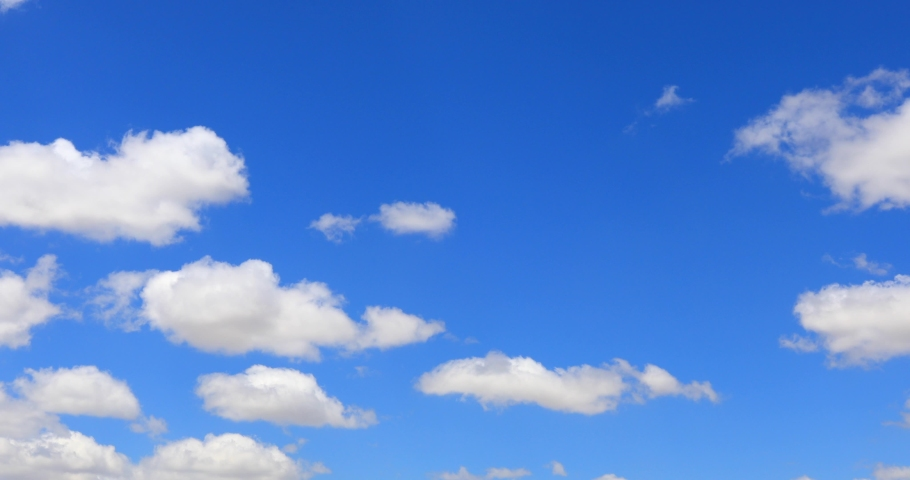 Cumulus clouds form against brilliant Blue skies sky atmosphere blue background puffy blue cumulus Royalty-Free Stock Footage #1053529190