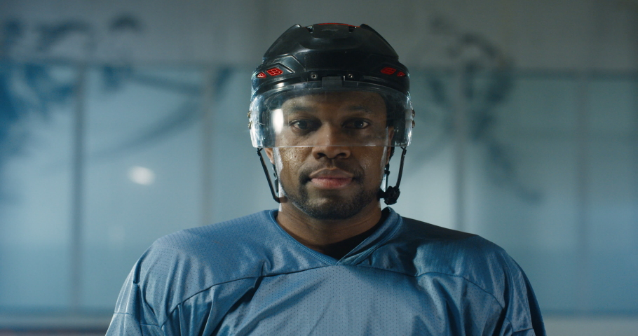 Close up of happy handsome young African American hockey player taking off helmet and smiling cheerfully on ice arena. Portrait shot of joyful good looking professional sportsman. | Shutterstock HD Video #1053530153