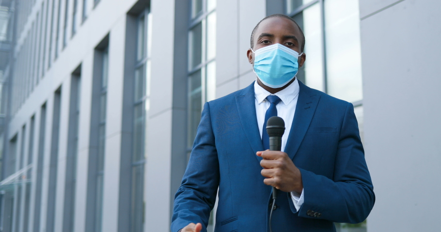 Portrait shot of young African American handsome male journalist in medical mask talking with microphone for news episode outdoor. Pandemic concept. Man correspondent in suit and tie and with mic. | Shutterstock HD Video #1053530537
