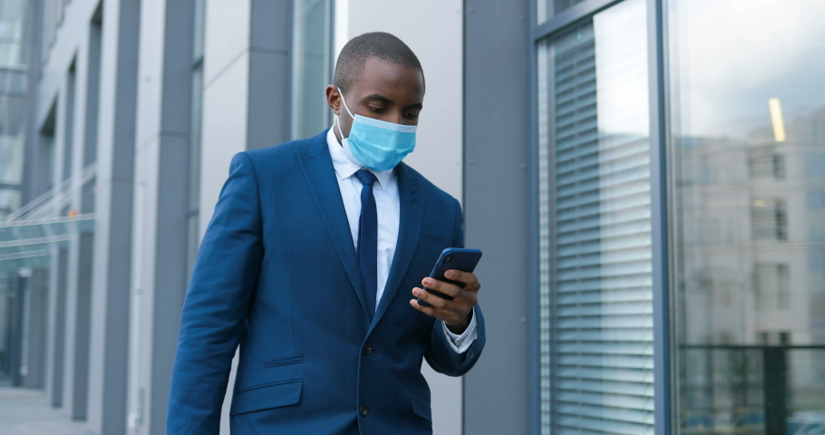 African American businessman in medical mask walking the street and texting message on mobile phone. Male pedestrian in respiratory protection strolling outdoor and tapping or scrolling on smartphone. Royalty-Free Stock Footage #1053530558