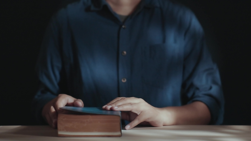 Spirituality and Religion Concept, Person Sitting on Desk to Making Pray on a Holy Bible in Church or House. Believe and Faith for Christian People. Dark Tone. Static Shot Royalty-Free Stock Footage #1053532466