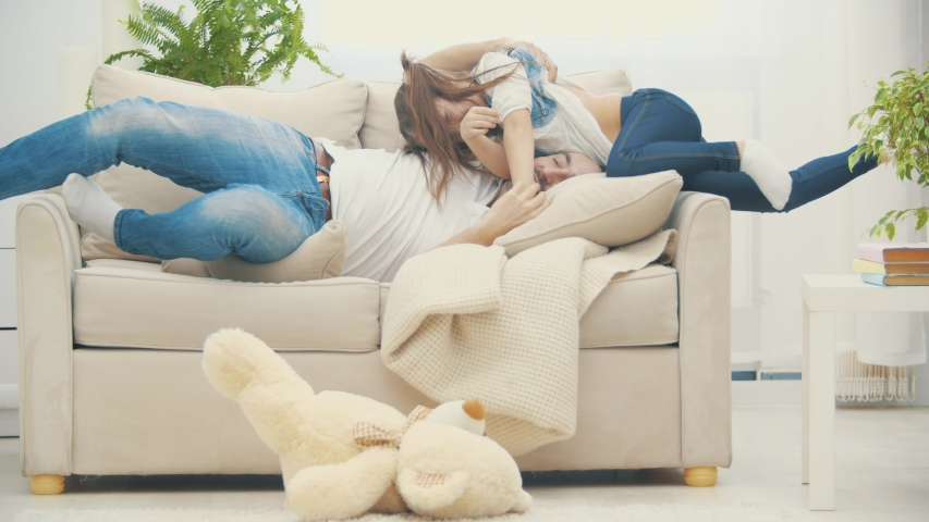 4k video where daddy is playing with his daughter laying on the sofa. Royalty-Free Stock Footage #1053533081