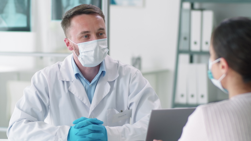 Male doctor in protective face mask, disposable gloves and lab coat speaking with female patient during medical consultation in clinic. Coronavirus pandemic concept