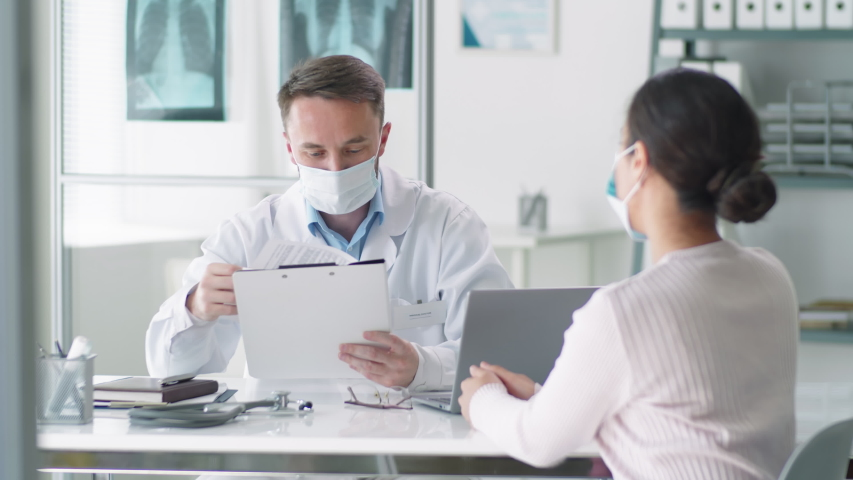 Male doctor in protective mask and lab coat sitting at desk in clinic, reading medical history of female patient and speaking with her during consultation. Covid-19 pandemic concept | Shutterstock HD Video #1053539963