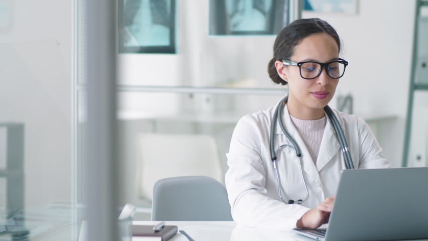 Attractive mixed-raced female doctor in lab coat, glasses and stethoscope over her neck using laptop at desk, looking at camera and smiling while working in medical office Royalty-Free Stock Footage #1053540566