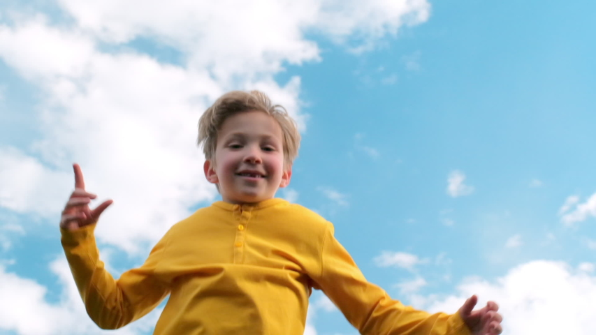 Happy child jumps very high on a trampoline against the blue sky. Blond boy jumps on a trampoline. Slow motion bottom view of a cheerful boy jumping on a trampoline. Children happiness.  | Shutterstock HD Video #1053548426