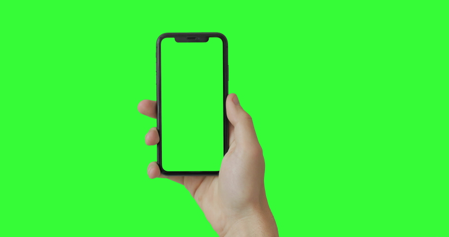 Man hand holding the smartphone on green screen chroma key background.  Mobile phone mock-up for your product. The iPhone Xr model in vertical orientation portrait mode. 2020 - USA, NY