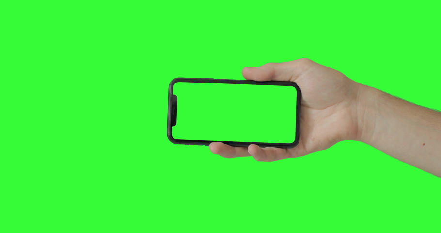 Man hand holding the smartphone on green screen chroma key background. Mobile phone mock-up for your product. The iPhone 11 model in horizontal orientation landscape mode. 2020 - USA, Miami