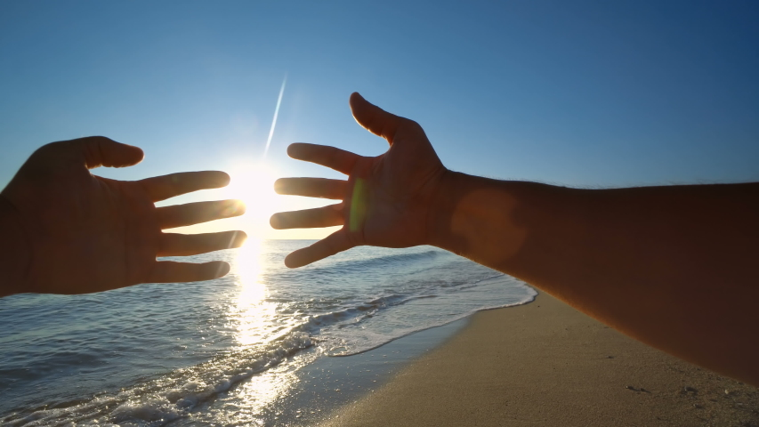 Two hands holding puzzle at beach sunset