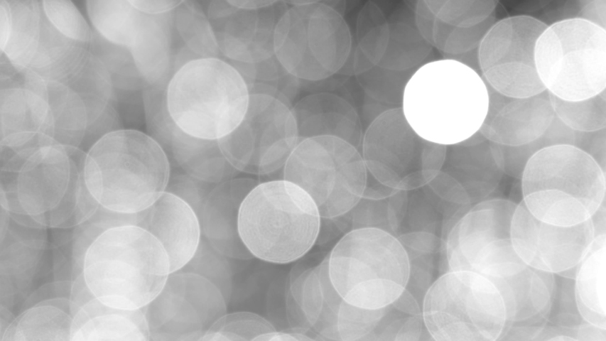 Blurred black and white abstract 4k video bokeh of blinking defocused holiday lights on dark background.  #1053549950
