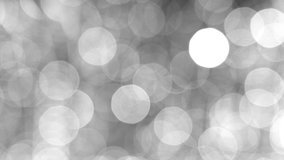 Blurred black and white abstract 4k video bokeh of blinking defocused holiday lights on dark background.