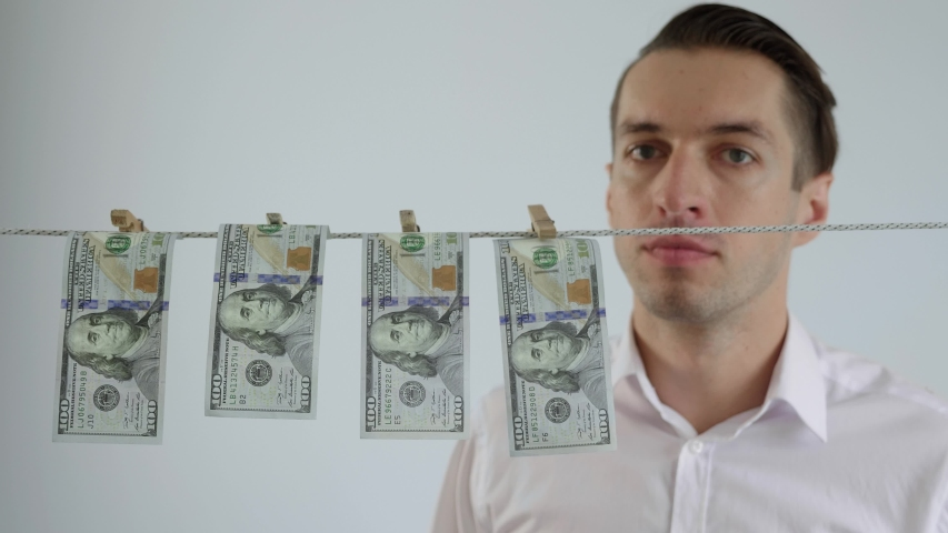 Businessman laundering money. Dollars dry on clothespin rope. The concept of money laundering. Financial fraud. Financial crime. Legalization of criminal proceeds. | Shutterstock HD Video #1053550391