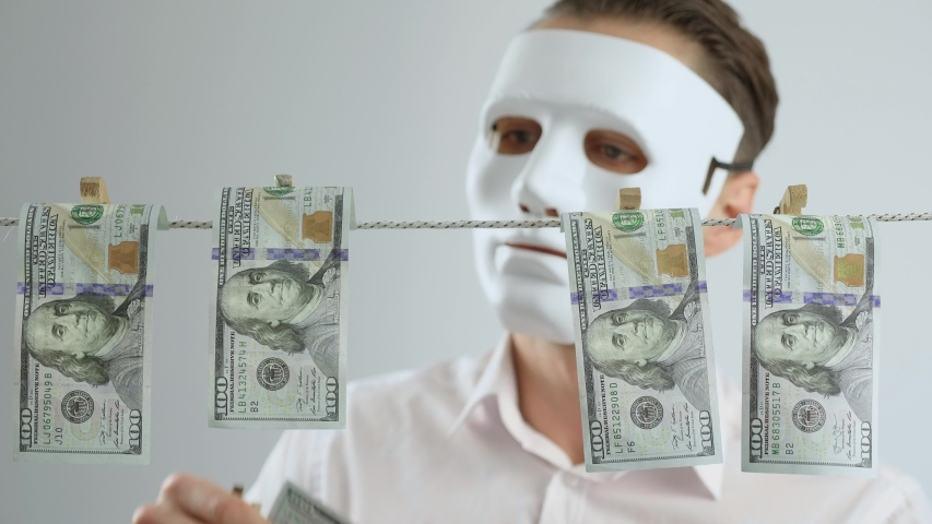 Masked anonymous laundering money. Dollars dry on clothespin rope. The concept of money laundering. Financial fraud. Financial crime. Legalization of criminal proceeds. | Shutterstock HD Video #1053550394