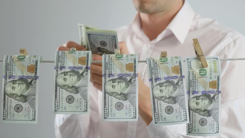 Man criminal counts money. Businessman in suit drying money. Corruption. Money laundering. Financial crime. Legalization of criminal proceeds. | Shutterstock HD Video #1053550409