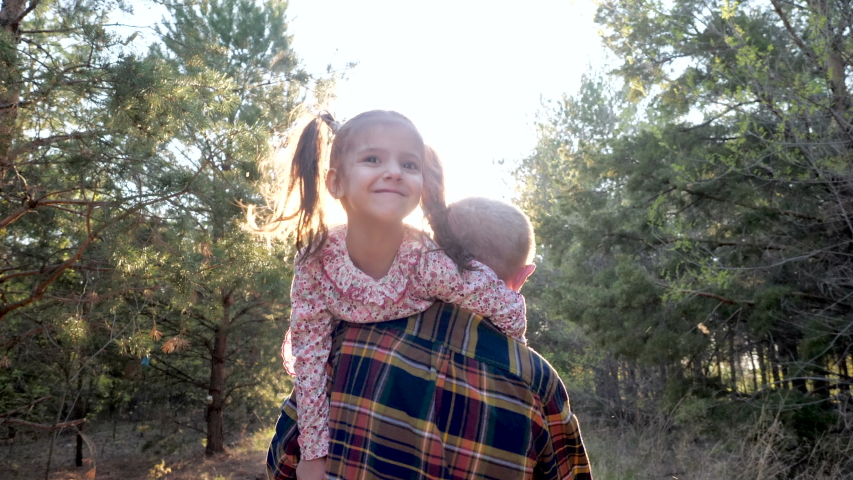 Back View at Old Grandfather Carrying Cute Smiling Child Girl on Shoulder, Walking in Summer Forest in Sunshine. Happy Lovely Family Plays Adventure Together, Fun Care for Little Grandchildren Outdoor | Shutterstock HD Video #1053551642