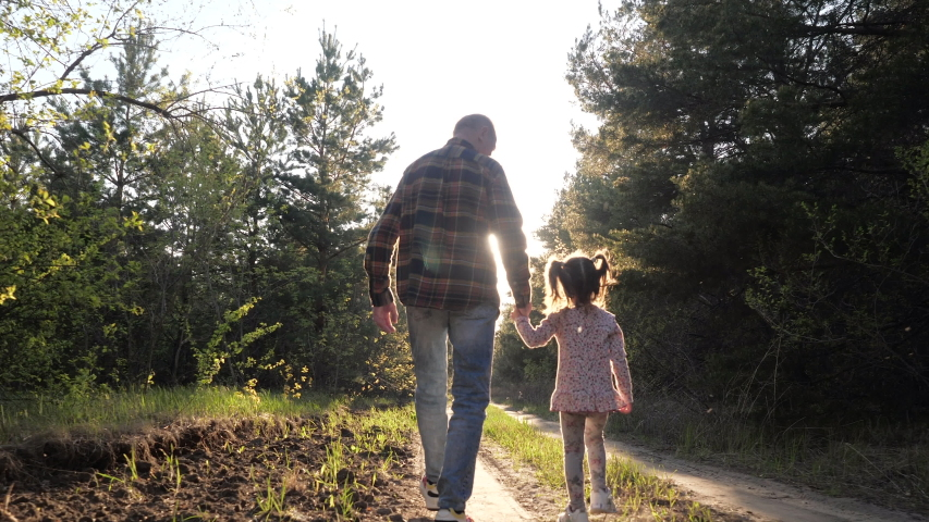 Rear View of Old Grandfather and Little Funny Talking Granddaughter Walking Along Summer Forest Path in Sunshine Holding Hands. Spend Leisure Time Together Outdoor for Carefree Lovely Family Happiness Royalty-Free Stock Footage #1053551654