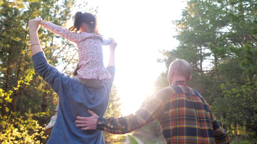 Rear View at Running Active Mother Rolling Little Funny Daughter on Neck with Support of Old Happy Grandfather in Forest Sunshine. Diverse Family Plays Plane Game Together, Walks Holding Hands Outdoor | Shutterstock HD Video #1053551663