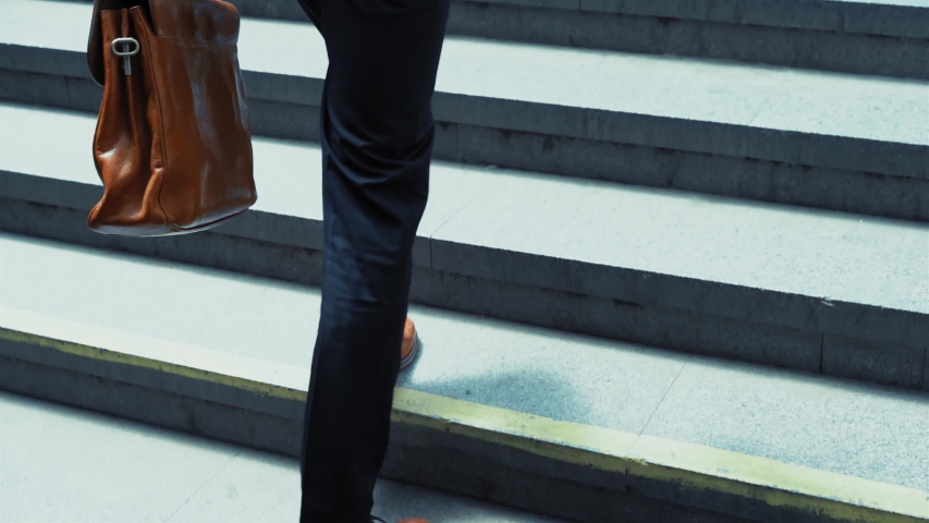 Close up on young man feet in a business suit runs upstairs out of the underground with a suitcase in his hand. Slow motion. Business on the go. Business concept. Prores 422.