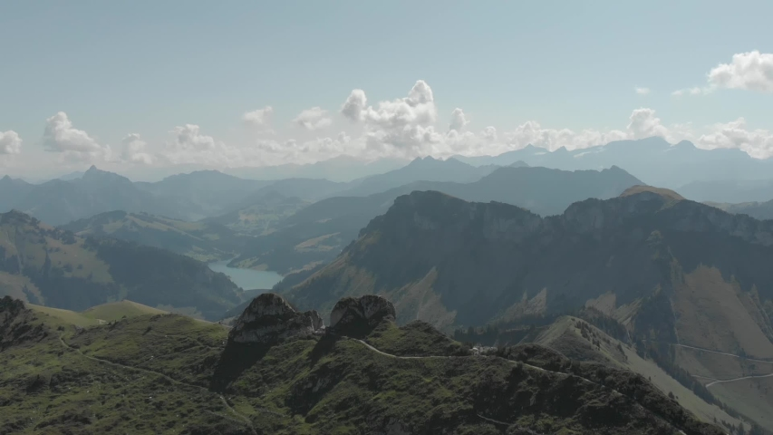 Aerial shot of Alps mountains. Mountains, peaks, cliffs, rocks, ridges, landscape, green grass, sky, clouds, nature, uncultivated nature, drone video.