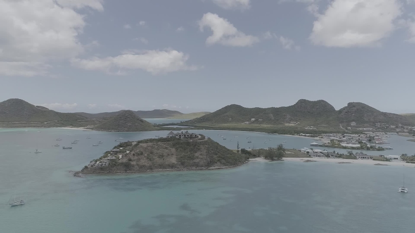 Aerial shot of Antigua and Barbuda. Sea, ocean, waves, coastline, sand, beach, palm trees, boats, corals, yachts, landscape, nature, drone video.